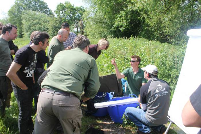 Brecht Morris of the Environment Agency shows a group of volunteers how to take scale samples for the Severn Predator Study Project.